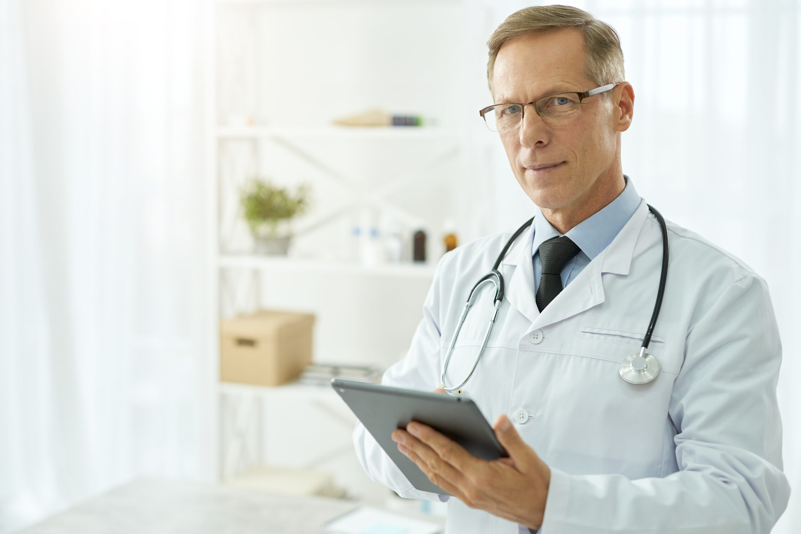 Handsome doctor in lab coat using tablet computer in clinic